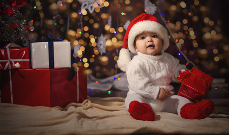 Kis mosolygós fiú (baby), fehér kötött pulóver és sapka mikulás a háttérben karácsonyi koszorú és díszdobozok szalaggal. Stock fotó