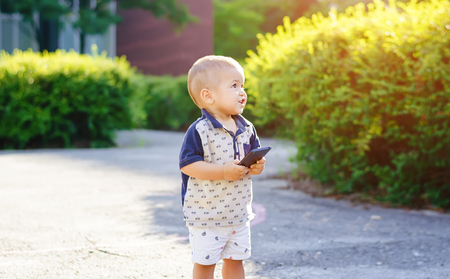 indignant: Little indignant boy with the phone in his hands outdoors. A walk in the street with green foliage.