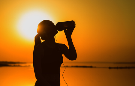 Silhouette of a young girl at sunset after jogging outdoors. Sportswoman drinks from a shaker.