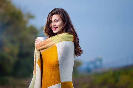 Young cheerful girl with a blanket on his shoulders and a cup of coffee (tea) in his hands. Autumn evening Stock Photo