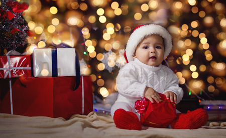 pullover: Little boy (baby) in a white knitted sweater and hat of Santa Claus on a background of Christmas garland and gift boxes with ribbon. Stock Photo