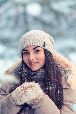 Young girl portrait in the winter forest. Walking girl in mittens and hat in snowy weather. Stock Photo