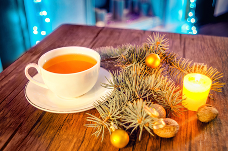 Cup of hot tea on a decorated table with candle and pine trees on a winter evening. Beautiful background.