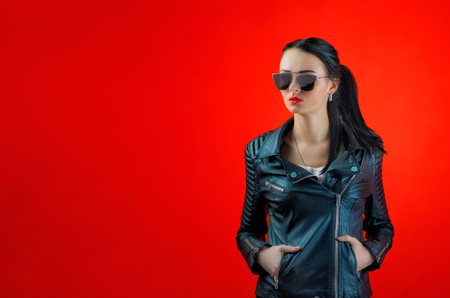 Strict young woman with black hair in a leather jacket and stylish sunglasses on a bright red background.