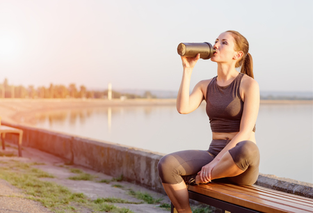 young girl of Caucasian appearance drinks a protein cocktail from a shaker after jogging in the open air. The bright sun illuminates it.
