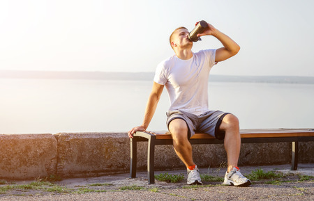young strong Caucasian man with white headphones drinks a protein cocktail from a shaker after running on open air. The bright sun illuminates it. Foto de archivo