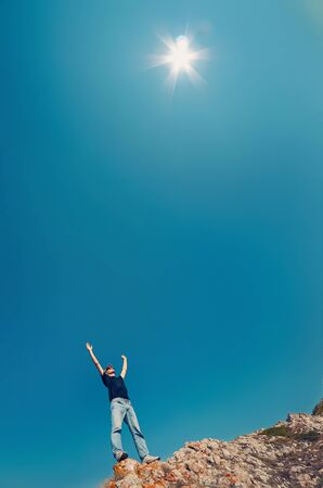 Young man  in jeans and black shirt on a mountain raised their hands to sky towards the sun. Travelling concept vertical  photo. Stock Photo