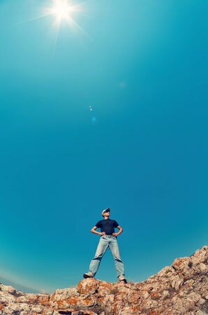 Young man  in jeans and black shirt on a mountain rock looking up into the sky.  Travelling concept photo.