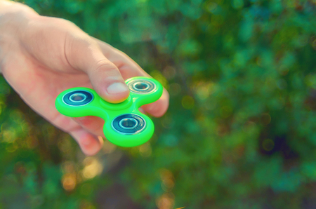 teenager hand holding  trendy antistress gadget fidget spinner. Man playing with green spinner outdoors  on the bright bokeh. Shallow DOF.