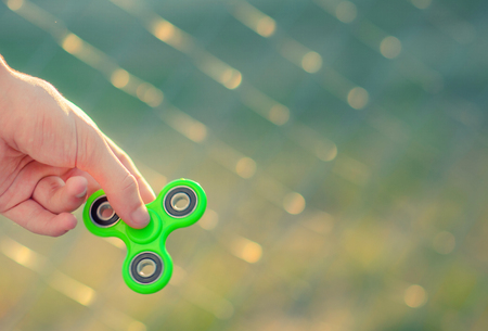 Young man hand holding antistress modern gadget fidget spinner. Teenager playing with green spinner outdoors on the rabitz grid bokeh. Shallow DOF.