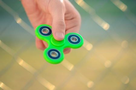 Young man hand holding antistress gadget fidget spinner. Teenager playing with green spinner outdoors on the rabitz grid bokeh. Shallow DOF.