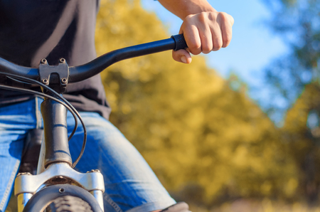 Close-up of a mans hand in jeans and a black T-shirt on the steering wheel of an off-road bicycle. Walk in the open air in the fall.