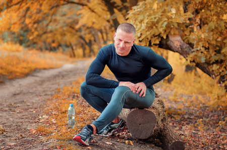 A young athletic  jogger in black tight fitting sportswears and  sneakers sits on a log, feels a strong pain in the muscle after cramping on a autumnall forest background.