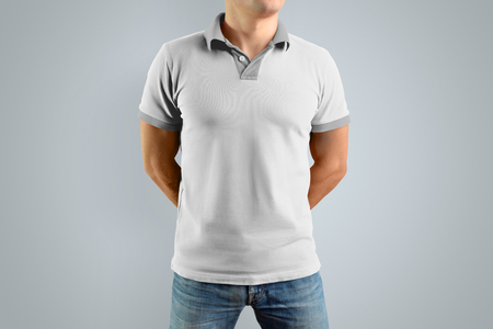 Slim man in the white polo shirt and blue jeans  isolated on the gray background, front view. Mockup for your graphic design. Archivio Fotografico