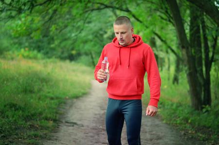 Un coureur athlétique mince dans une veste rouge avec une capuche et des leggins de sport noirs tient dans le flacon à main avec de l'eau après avoir fait du jogging sur une forêt de printemps verte.