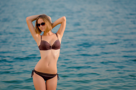 Sexy  beautiful  caucasian young woman in a glasses on the beach, is standing on azure water. Recreation and pampering on the seashore (ocean, river, lake) in sunset light.