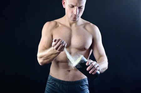 Strong muscular athlete pours protein nutrition supplement into a black plastic shaker on a dark studio background. Stock Photo - 121875046