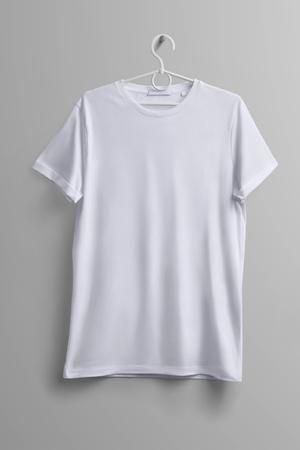 Maquette de studio de vêtements. T-shirt blanc accroché à un cintre en plastique avec des ombres sur fond gris. Le modèle peut être utilisé pour votre conception. Banque d'images