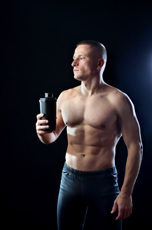 Athletic  brawny sportman  holds a black shaker with protein  in his hand. Guy poses on the dark  background.