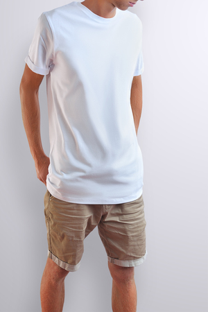 Attractive slim guy  in a blank T-shirt and cotton brown shorts on a white studio background. Frontal pose. Mockup can be use in your showcase. 免版税图像