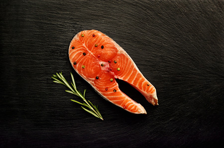 Fresh raw salmon steak slice with fragrant pepper and sprig of rosemary on black slate board background. Diagonal food fish composition top of the view.