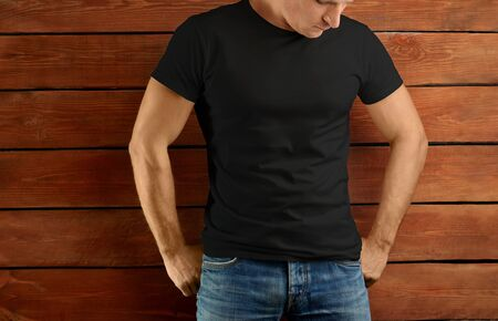 Mockup clothes. Athletic fit guy in a black T-shirt and blue jeans on a brown wooden studio background. Template ready for you design