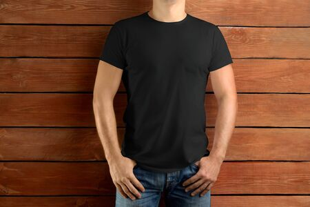 Mockup clothes. Sport slim man in a black T-shirt and blue jeans on a brown wooden studio background. Template ready for you design Reklamní fotografie