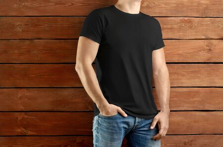 Mockup clothes. Brawny slim  man  in a black T-shirt and blue jeans on a brown wooden studio background. Template ready for you showcase.