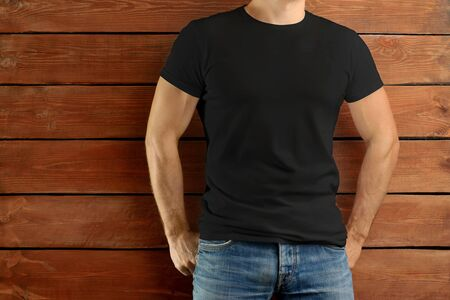 Mockup clothes. Athletic fit guy in a black T-shirt and blue jeans standing on a brown wooden studio background. Template ready for you design
