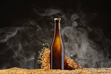 Drink mockup series. Brown beer bottle with reflections on a smoke black studio background with scattering wheat corns. Template ready to use on your showcase.