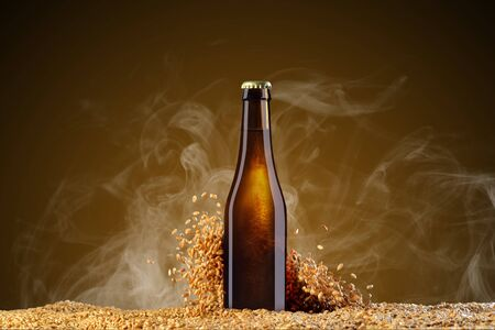 Drink mockup series. Brown beer bottle with reflections on a smoke umber  background with scattering wheat grains. Template ready to use on your showcase.