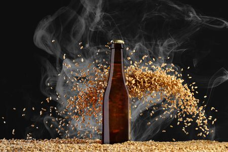 Drink template series. Brown beer bottle with reflections on a  smoke black  background with heavily scattering wheat grains. Mockup ready to use on your design. Reklamní fotografie
