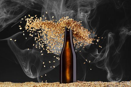 Drink template series. Brown beer bottle  with reflections on a  smoke dark  background  with gracefully scattering wheat grains. Mockup ready to use on your showcase. Reklamní fotografie