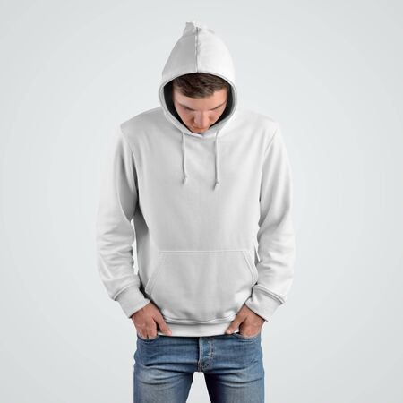 Front view of a white hoodie mockup on a young guy with his head bowed.Template of casual clothes for presentation in the store.