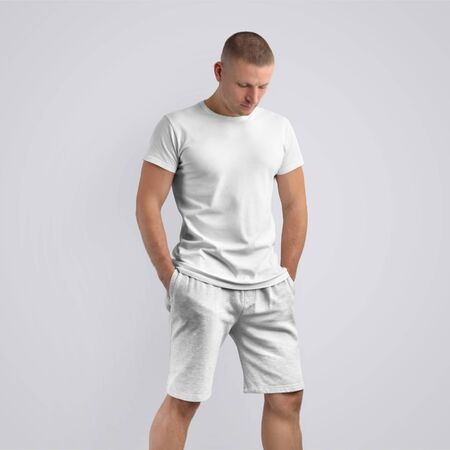 Stylish slim model  in a blank T-shirt and knitted grey shorts on a white studio background. Frontal pose. Template can be use in your design.