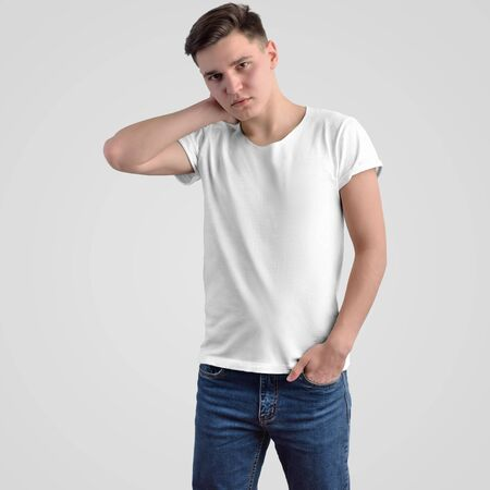 Template white men's t-shirt on a young guy on a background in the studio. Mockup clothes for presentation of design and advertising in the online store. Front view. 免版税图像