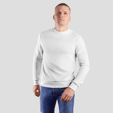 Mockup of a clean sweatshirt on a sporty man, in blue jeans, walking forward, on a white blank background. Template textile clothes for presentation design and print. Фото со стока