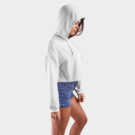 Mockup of a white crop top on a model with her head bowed, in blue shorts, women's sweatshirt for presentation of design, side view. Template of an empty hoodie on a young girl isolated on background