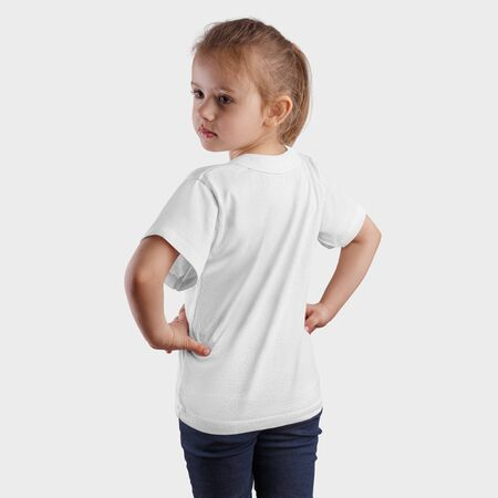 Mockup of a white T-shirt on a standing pretty girl, turning her head back, fashionable baby clothes for presentation of design and pattern. Clothing template on a beautiful kid isolated on background