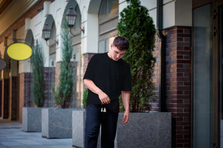Male black t-shirt template on a guy posing against a blurred street background, in urban clothes for a design presentation. Short sleeved clothing mockup, front view, for advertising in an online store