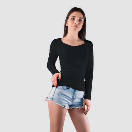 Black sweatshirt template on a girl in shorts, front view, fashionable clothes with long sleeves, for design presentation. Casual pullover mockup for women isolated on background, front view
