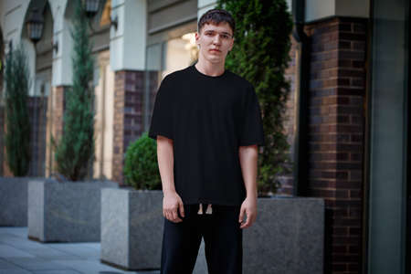 Mockup of a black T-shirt on a guy in dark pants, stylish clothes in an urban style on a blurred street background. Blank short sleeve clothing template for design presentation, pattern, front