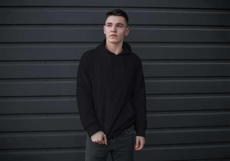 Mockup of a black men's sweatshirt with a pocket on a guy on a metal wall background, front view. Blank casual clothing template for design presentation, advertising sweatshirt. Urban style