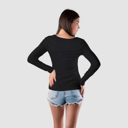 Mockup of a black sweatshirt, women's clothing with a long sleeve on a girl in shorts, back view, isolated on background. Template for branded pullover, casual wear for design presentation, advertising