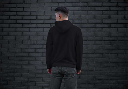 Template of black men's clothing with long sleeves on a young guy on a brick wall background, back, sweatshirt with a hood. Hoodie mockup for design presentation, advertising in the store.Urban style Banque d'images