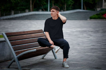 Black T-shirt template on a guy sitting on a blurred square background, on a bench, clothes front view. Mockup of men's clothing for design presentation, advertising in an online store.Urban style