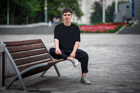 Mockup of a black casual t-shirt on a guy sitting on a blurred background of a park, on a bench, front view, for design presentation. Blank clothing template for online store advertising.Urban style