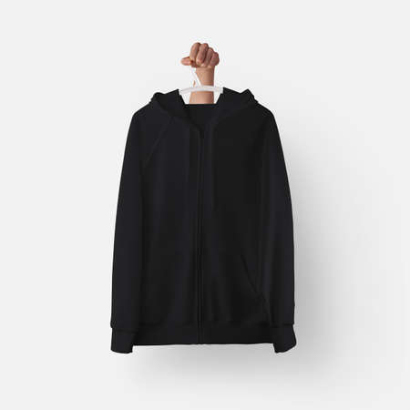 Black textured hoodie template with zipper, pocket hanging on a plastic hanger in hand, front view for design presentation, print. Mockup of casual clothes isolated on background. Men's clothing