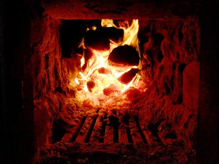 brazier: Photo of fire brown wood dark green black coals on bright yellow fire inside metal brazier.