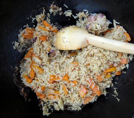 Picture of cooking pilaf on black bowl.